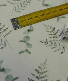 Jersey de coton feuillage vert tendre sur fond blanc (1.4€/10cm)